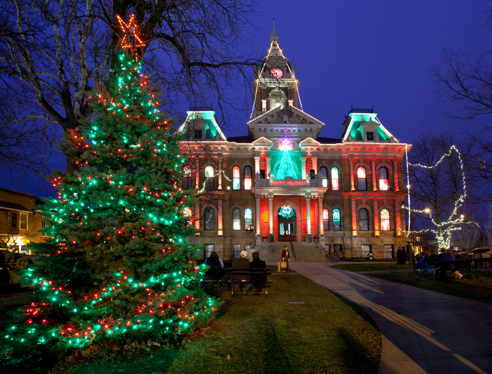 Evergreen tree decorated with red and green lights. Large ornate building in background decorated with red and green lights.