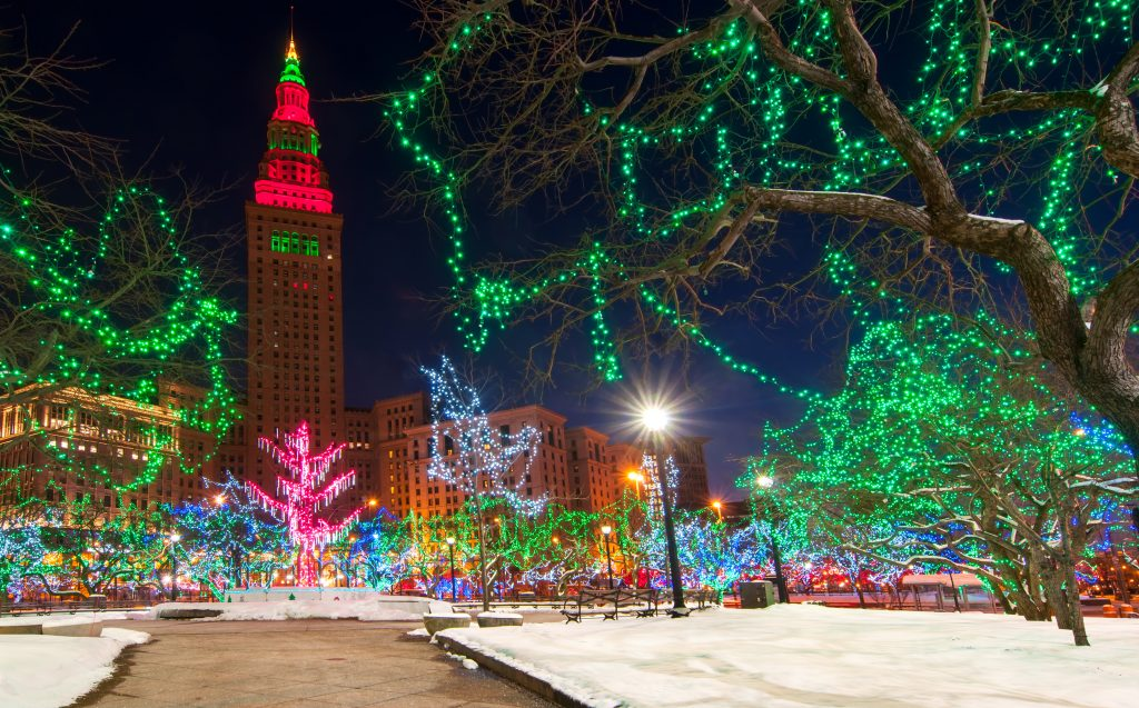 Colorful Ohio Christmas lights on trees with snow on ground. City buildings in background.