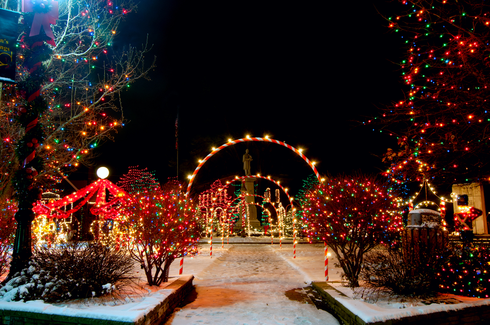 Brilliant Christmas lights in Ohio with illuminated arches, trees, with snow on ground.