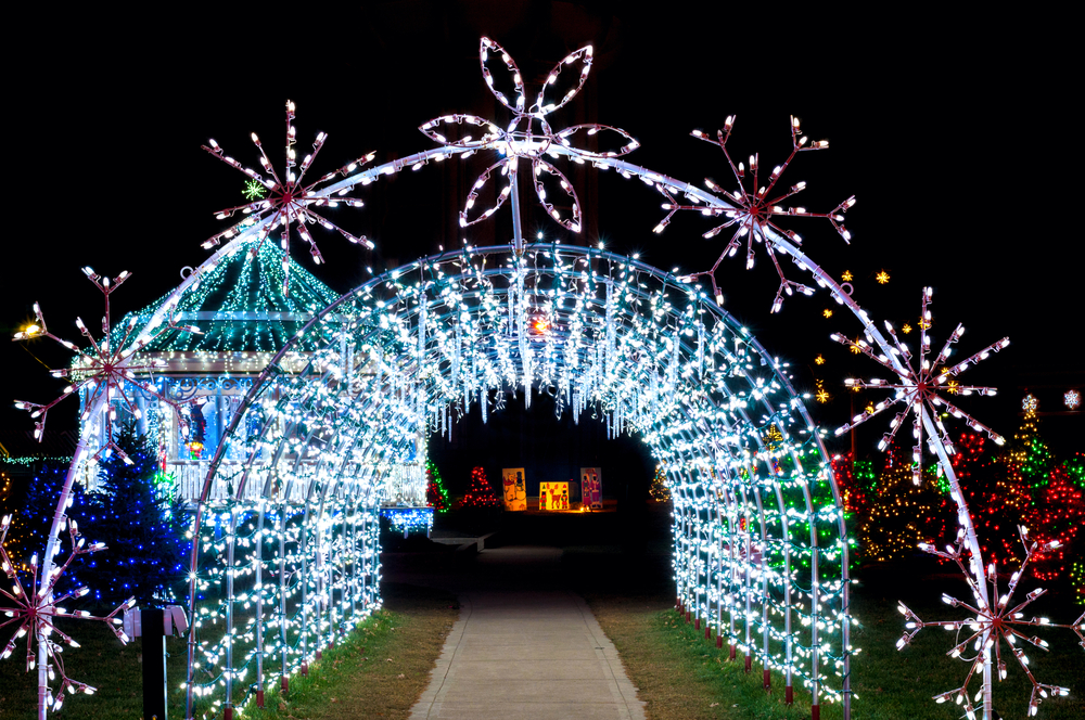 Tunnel of white lights adorned with large snowflake lights.