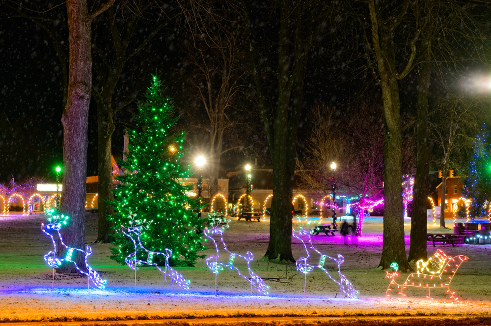 Beautiful Ohio Christmas display  illuminated green lights on evergreen tree, Santa and his reindeers in foreground, snow on the ground.