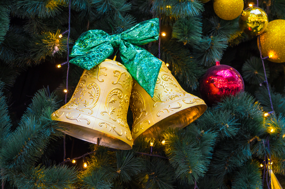 Gold Christmas bells with green ribbon hung on evergreen tree.
