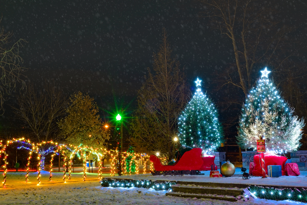 Two large Christmas trees with white lights, red sleigh and large ornaments in front of them, and yellow illuminated tree tunnel to the left.