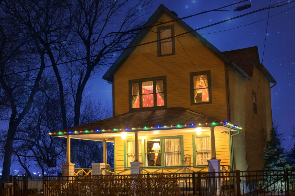 Yellow house with green trim, large front porch with multicolored lights, two windows on second floor illuminated. Christmas in Ohio.