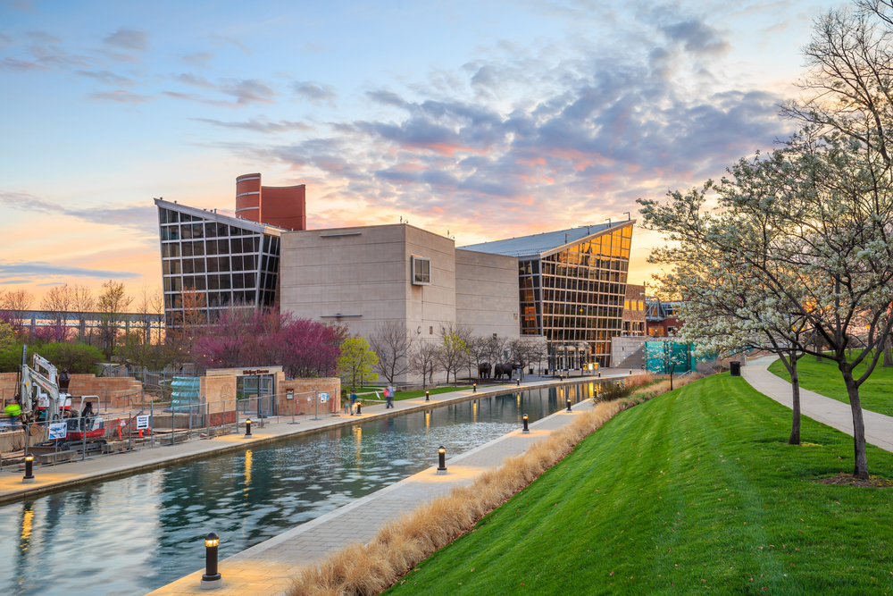 Outside of the Indiana State Museum with a canal in front and flowering trees at sunset.