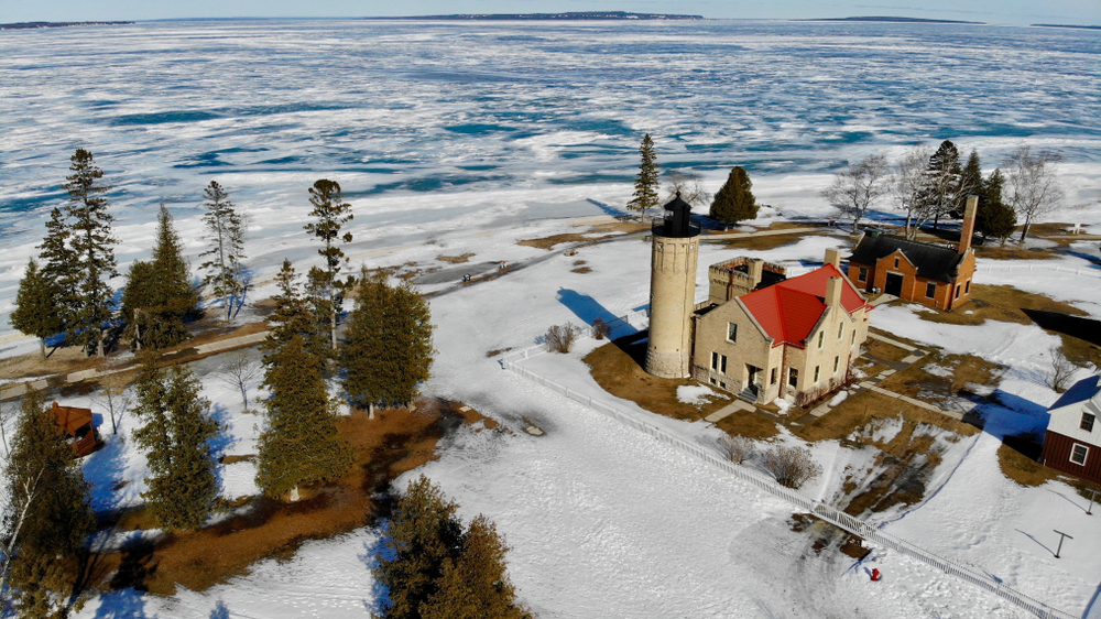Aerial photo of McGulpin Point Lighthouse and Lake Michigan with snow.
