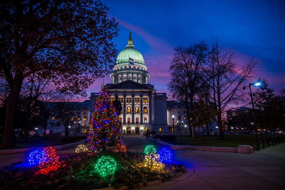 The Wisconsin State Capitol at sunset with a Christmas tree in front.