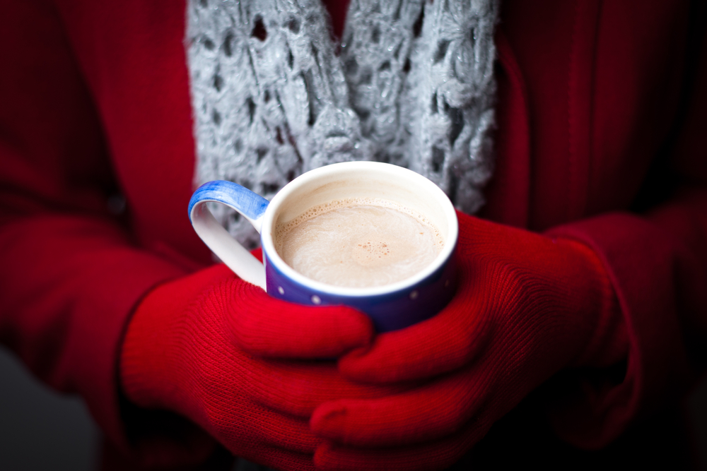Woman with red gloves holding a mug of hot cocoa.
