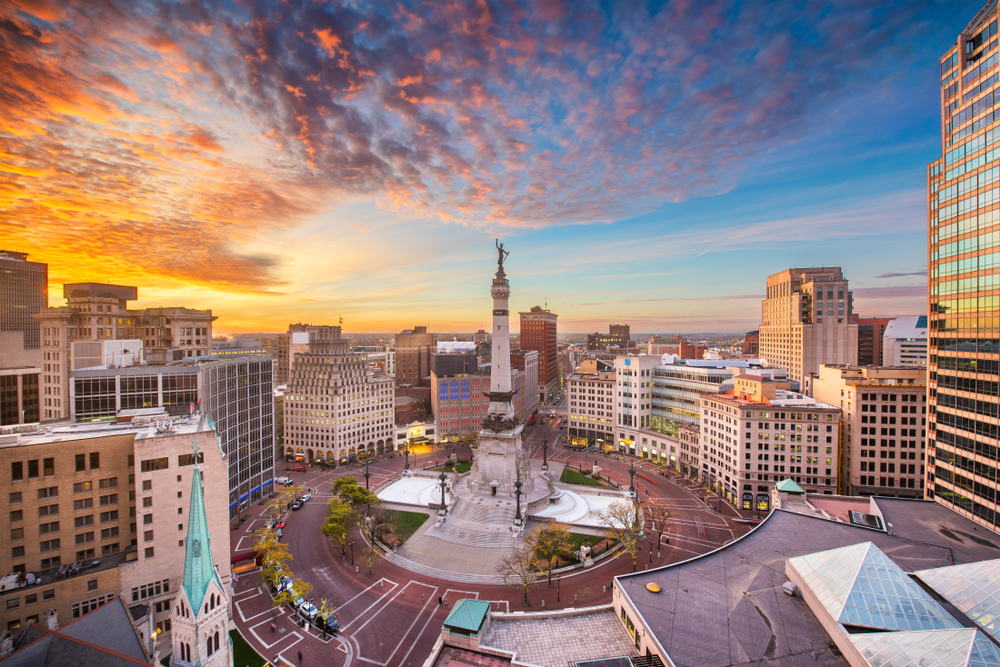 Aerial photo of Monument Circle surrounded by skyscrapers during sunset.