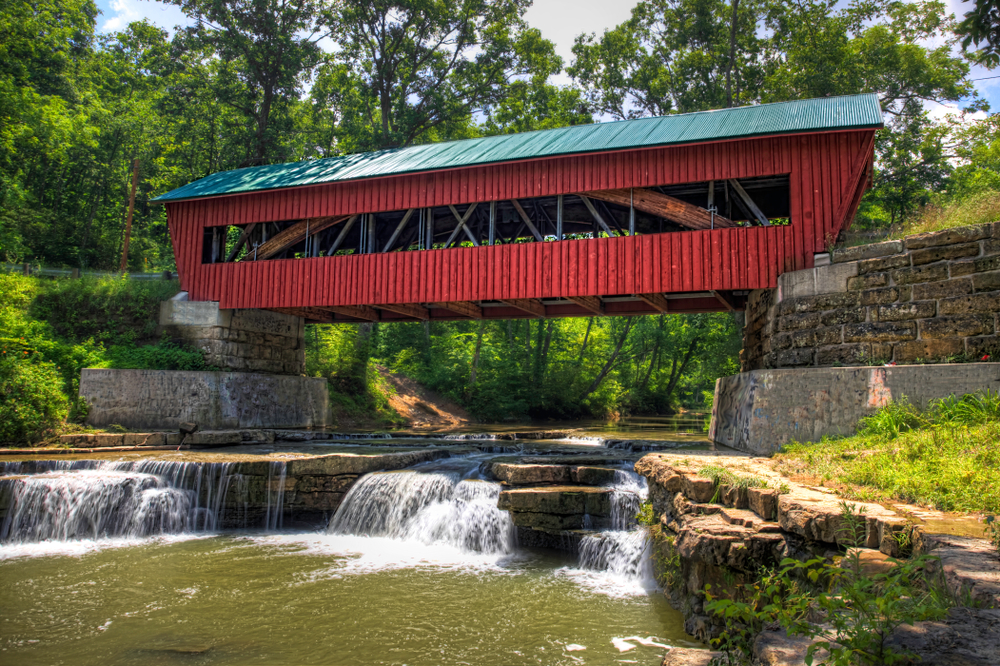 Red wooden bridge covered with green roof, spanning river with small waterfalls in foreground. Weekend getaways in Ohio.