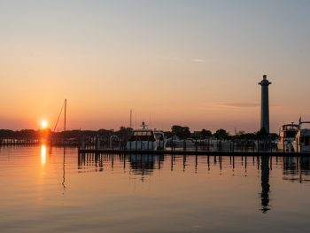 sunrise over marina with boats and monument