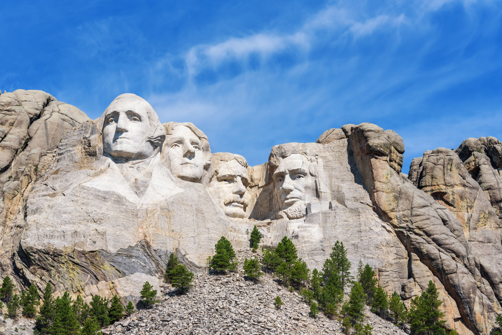 Four faces/heads of men carved into side of mountain with blue sky in background and evergreen trees at base of mountain.