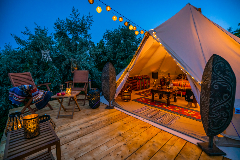 Tent with white romantic white lights and candles on deck with brown patio furniture and glasses of wine with apples.