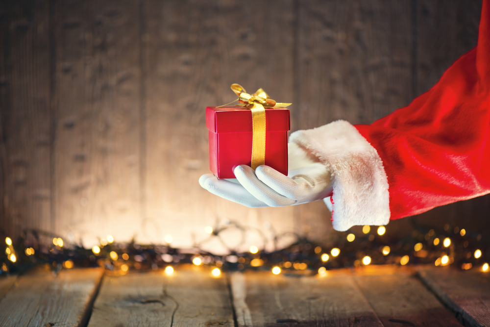 Santa Claus's arm reaching into the frame holding a wrapped present.