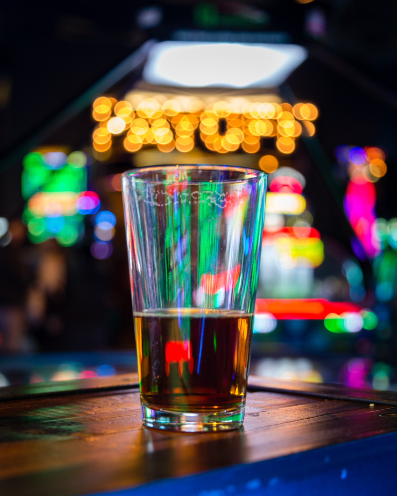 A beer glass in front of arcade lights.