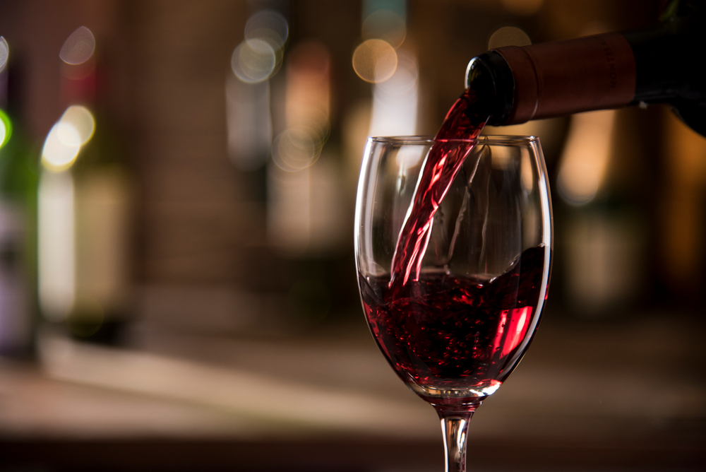 Close up of wine being poured into a glass.