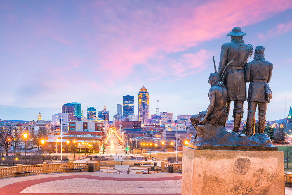 A sculpture of historic figures looking out over the Des Moines skyline at sunset.