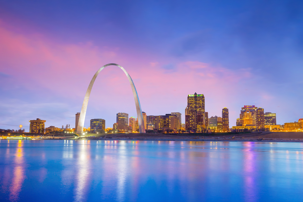 The St. Louis skyline with the Gateway Arch and a pink and purple sky and water.