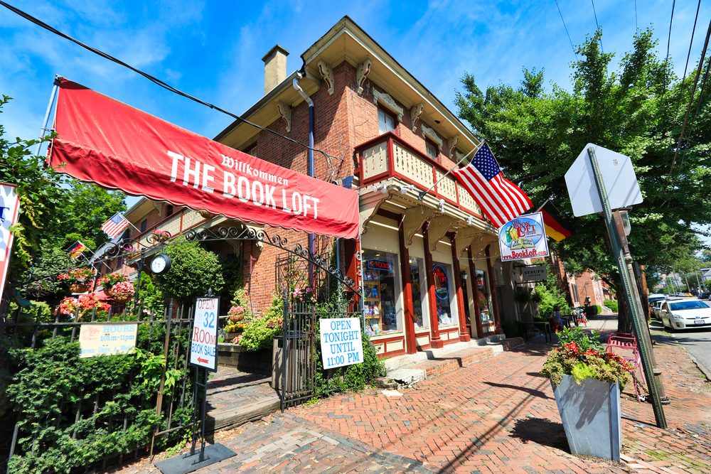 """The book loft is pictured on a brick sidewalk.  The store has German balconies and a big red sign that says """"Wilkommen The Book Loft"""""""