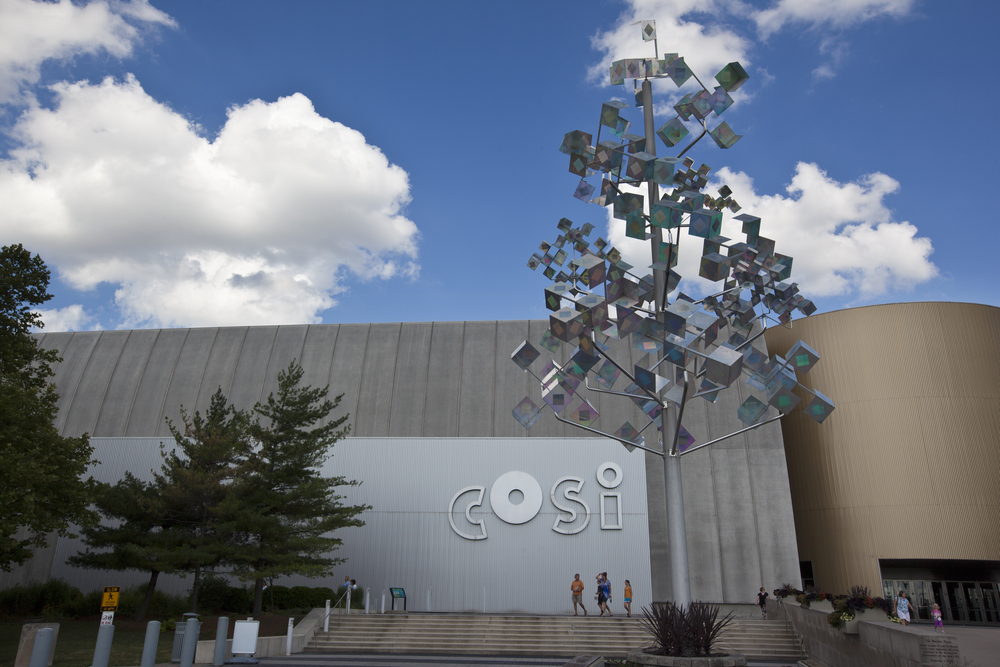 An industrial looking building, the Center of Science and Industry, is pictured as one of the best things to do in Columbus Ohio.  The building features the acronym COSI in silver lowercase letters.  A holographic statue that looks like a tree stands in front of the building.