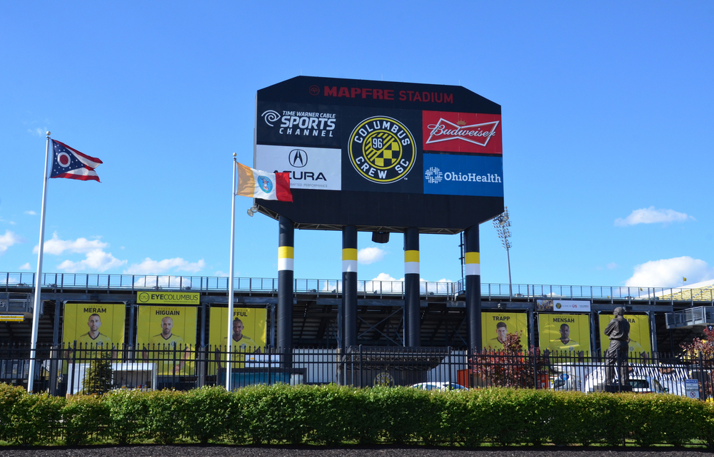 The Columbus Crew stadium is pictured with flags in front.  The players are pictured on banners, and the Crew's sponsors are on a billboard.  Columbus Crew games are one of the best things to do in Columbus Ohio