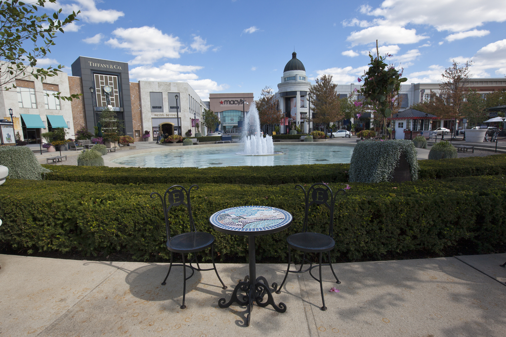 This photo features a wide shot of Easton mall.  In the foreground, there is a table with two chairs.  The mid ground has a fountain surrounded by a hedge.  The background has large stores like Macy's and Tiffany & Co.  Easton is one of the best things to do in Columbus Ohio.