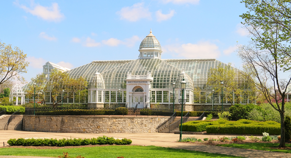 Franklin Conservatory, one of the best things to do in Columbus Ohio, is pictured here.  It is a large white and glass greenhouse with a turret in the center.