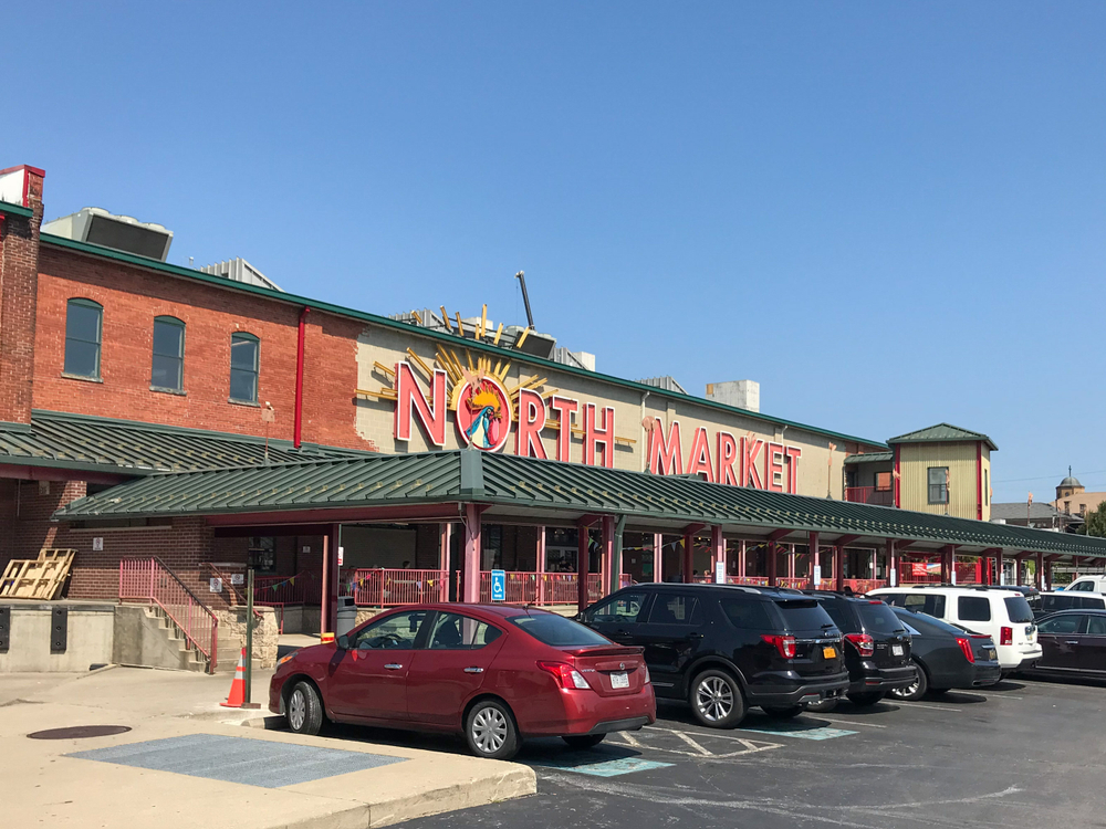 """A building with green awnings is pictured with cars parked in front.  The building has the words """"North Market"""" displayed in bold red lettering.  The """"O"""" has a depiction of a rooster crowing inside."""
