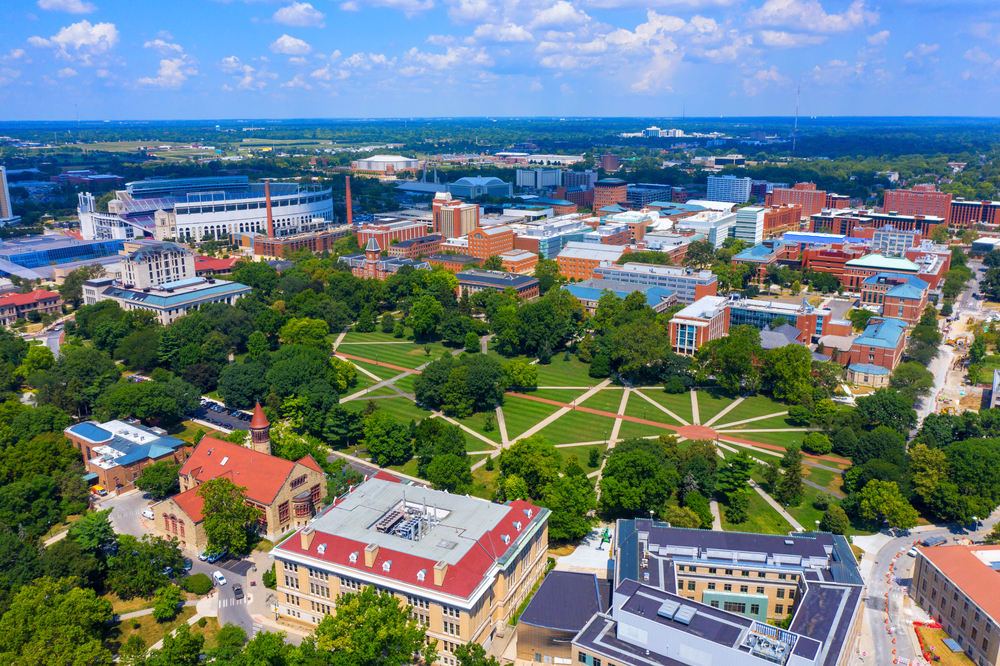 An aerial shot of The Ohio State University is depicted with many buildings and a lot of green space and trees.  The main quad on campus, the Oval, is the central focal point of the picture, notable for its abstract sidewalk pattern.