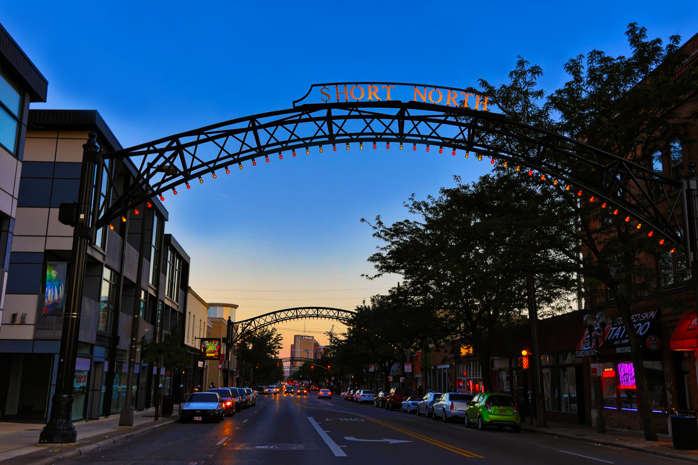 The short north, one of the best things to do in Columbus Ohio, is depicted at sunset.  Buildings line High Street as iron arches sprawl across the road with small lights on them.