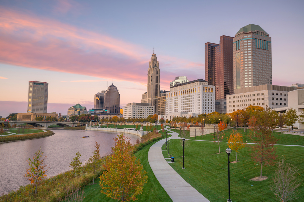 This picture features the urban trails, one of the best things to do in Columbus Ohio.  The trails wind through green spaces and skyscrapers as depicted at sunset in this image.