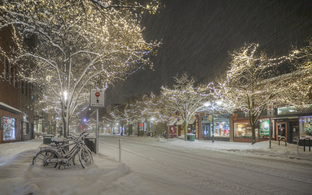 Downtown Traverse City at night with snow and lights in the trees.