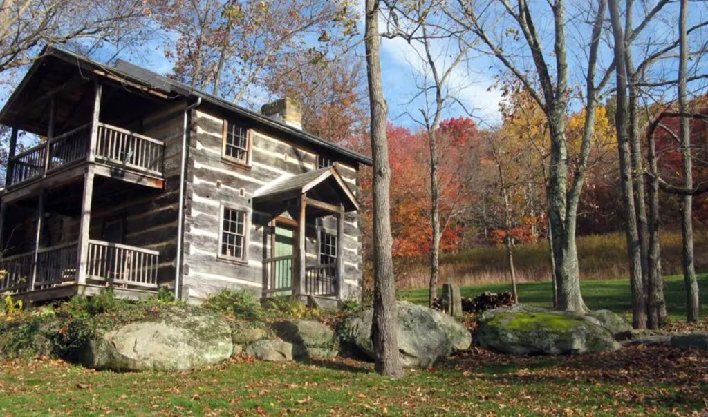 Large cabin VRBO in Ohio with front porch and balcony, large boulders in foreground and autumnal colors in background.