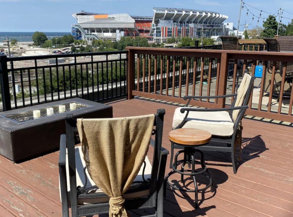 Balcony of Ohio VRBO overlooking stadium with lake in background. Patio chairs and small table in foreground.