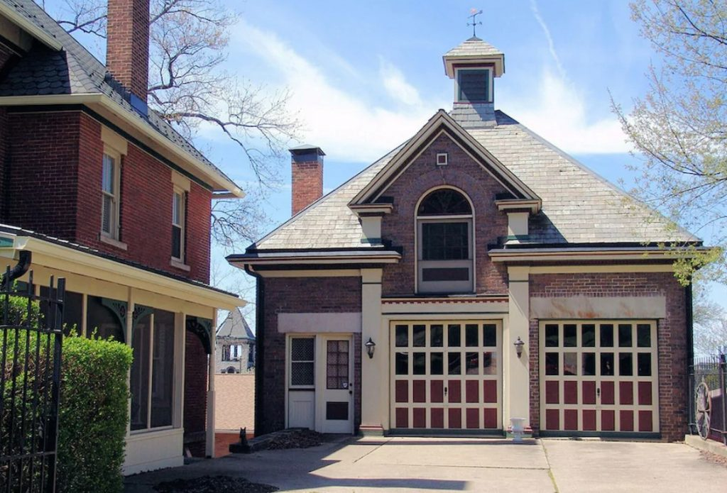 Red brick house with decorative garage doors, white columns, cupola on roof.