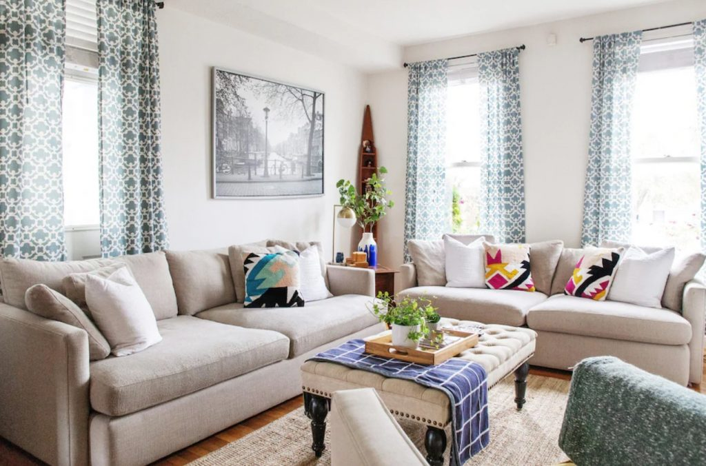 Stylish living room with gray couches, large windows with blue patterned drapes. Ohio VRBO.