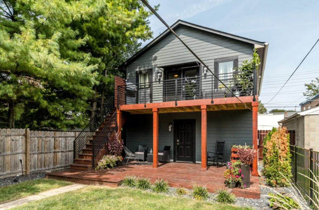 Grey house with wooden patio and wood columns, black wrought iron railing leading to upstairs.