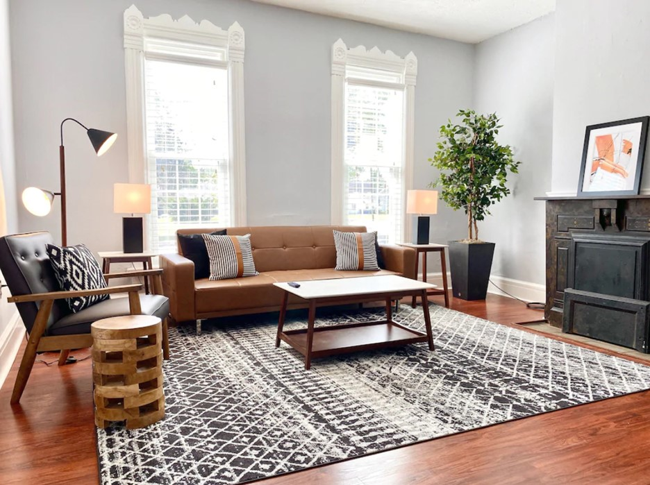Bright living room with brown couch, patterned rug and wood floor. Large windows in background.