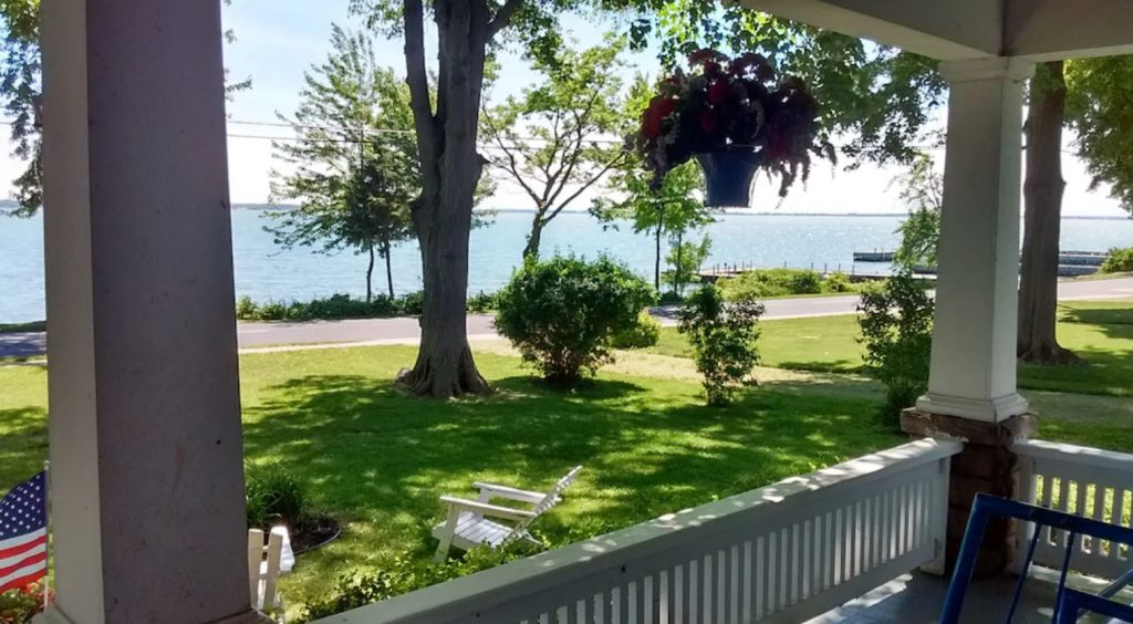 View of water from front porch with white columns, green manicured front yard. Pretty VRBO in Ohio