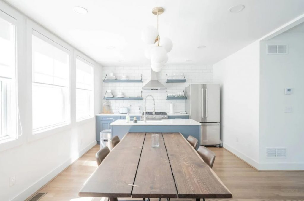 Understated kitchen dining area with long brown wood plank table in foreground, white kitchen with pale blue cabinets in background.