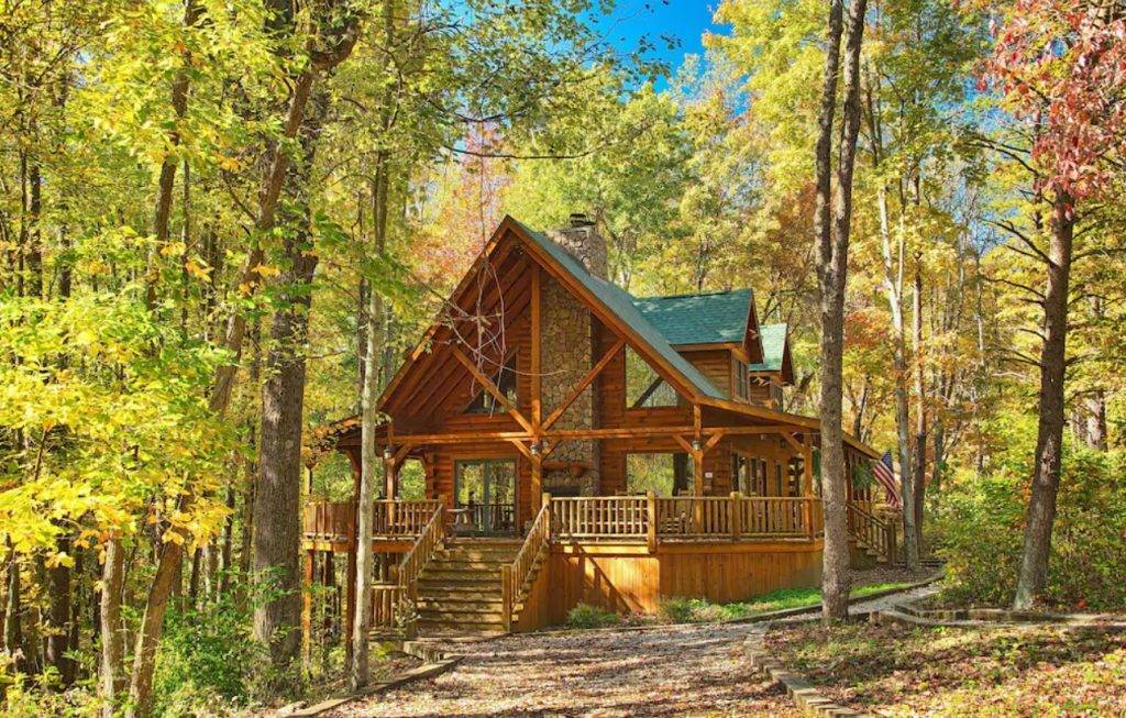 Red rustic cabin with A-frame roof, stone chimney and large floor to ceiling windows. VRBO in Ohio