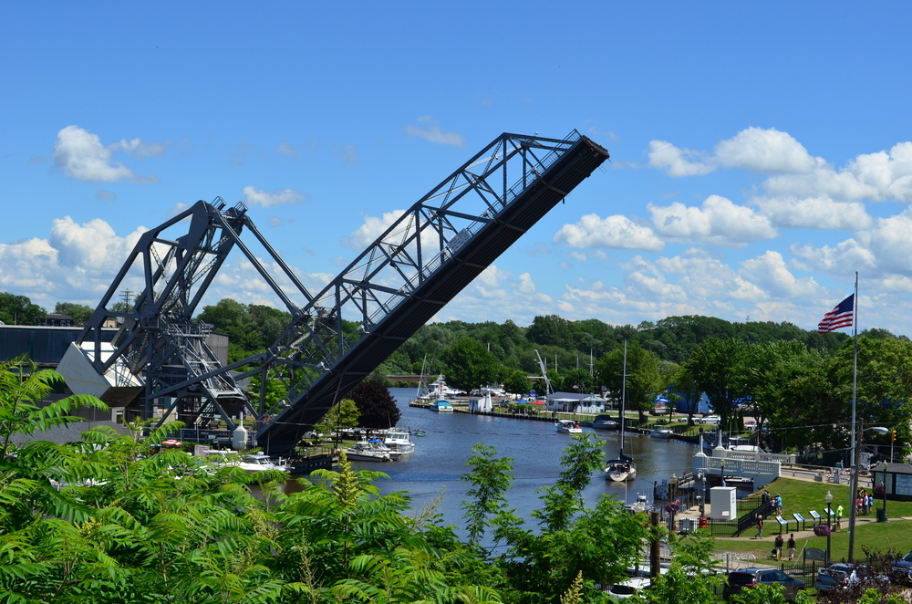 Large iron  bridge lifted up for ships in river below to cross under. Boats in water and blue sky in background. Weekend getaways in Ohio.