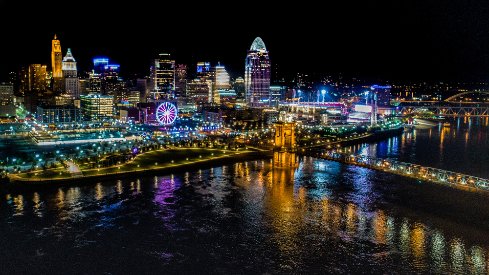 Ohio city at night illuminated with beautiful lights with water in foreground.