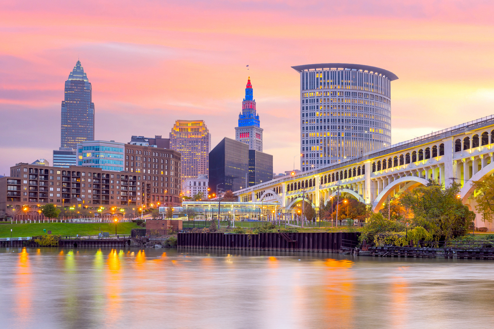 City skyscrapers and arched bridge illuminated with pink sunset sky in background.