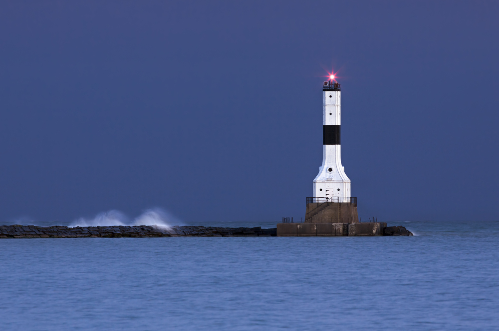 White and black lighthouse at end of stone wall with water splashing over it