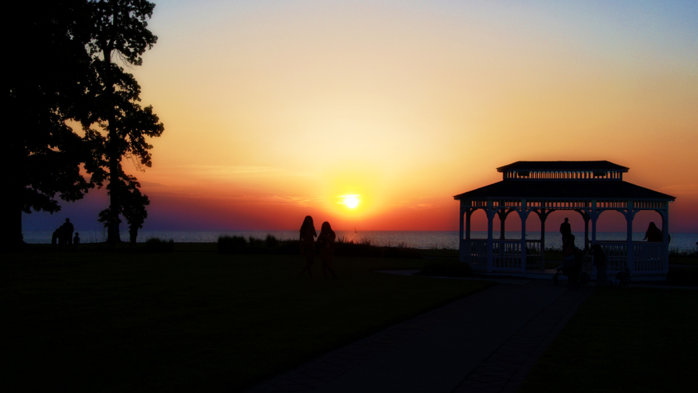 Brilliant orange and yellow sunset with pavilion on right and people on beach in background.