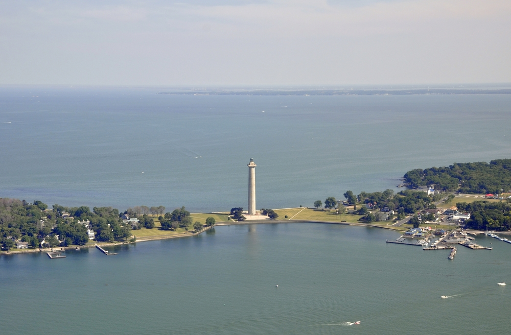 Aerial view of tall white monument with trees and land on either side, with water in background and foreground. Weekend getaways in Ohio.