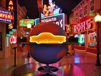 Looking down a row in a museum that looks like a city street where you find tons of old signs and neon signs. In the middle is a sign that is a large globe that sits on the ground and has a neon yellow car on the middle of the globe. One of the best hidden gems in Ohio.