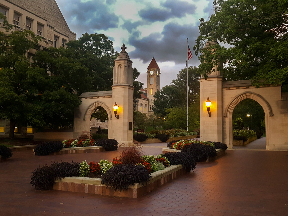 A brick courtyard with flower beds that have red and white flowers in them. There are also stone arches that lead to another part of the courtyard and trees. In the distance you can see a clock tower. One of the best weekend getaways in Indiana.