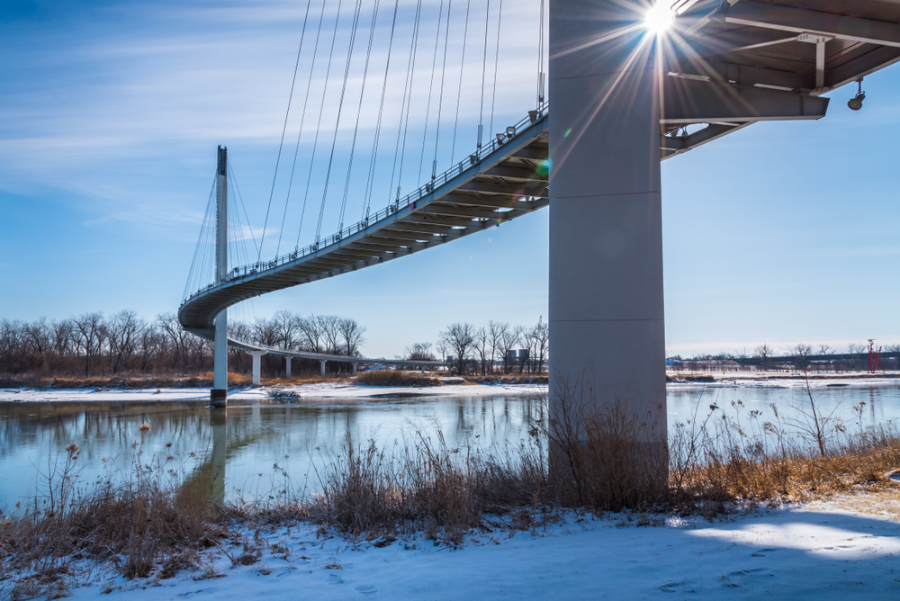 Looking at the Bob Kerrey Pedestrian bridge from the shores of the Missouri River. You can see the bridge curving over the river and going over a small island before continuing on. The bridge is white with suspension wires. The shore of the river is covered in snow. Its one of the most fun things to do in Omaha.